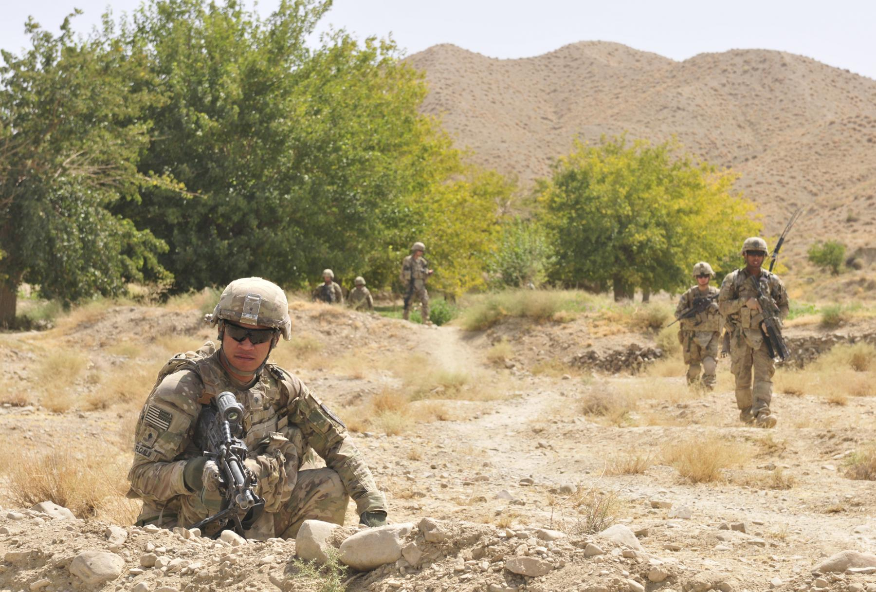 An infantryman provides security for members of his platoon.